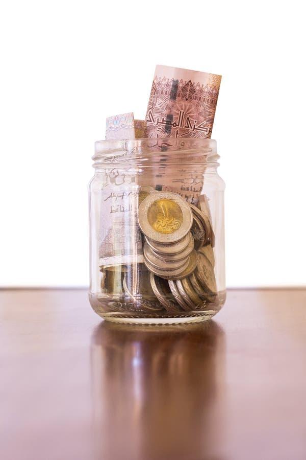 Monedas y billetes de banco en tarro, libras egipcias, en el aislador de madera del escritorio fotos de archivo libres de regalías