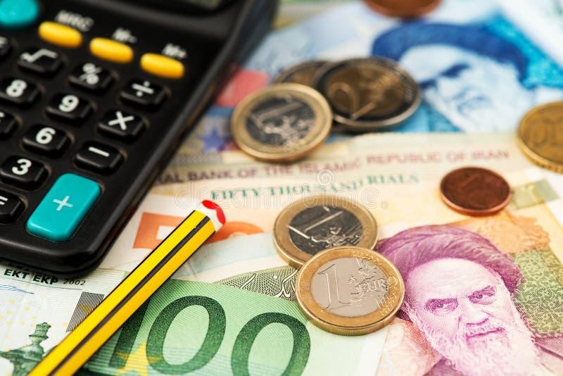Monedas y billetes de banco euro con moneda del rial iraní Dinero EUR de Europa Irán al IRR imagen de archivo libre de regalías