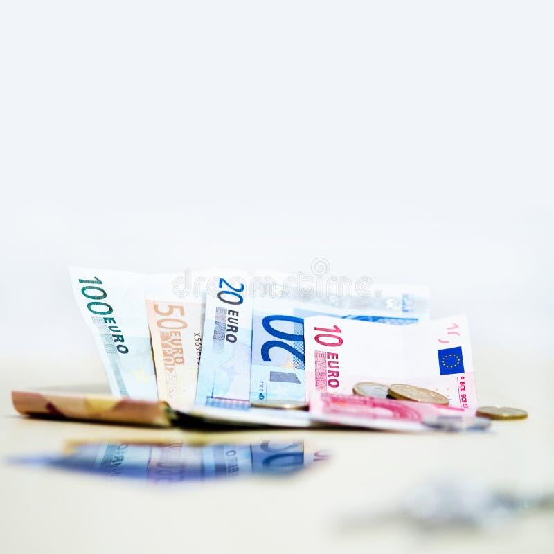 Monedas y billetes de banco euro del dinero en el fondo blanco en cuadrado imagen de archivo libre de regalías