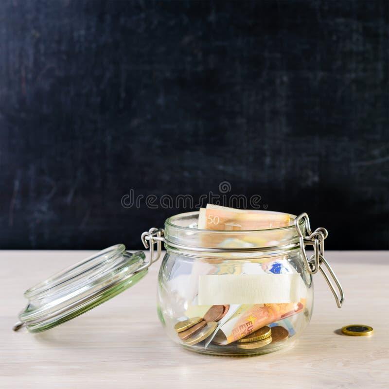 Monedas y billetes en un tarro de cristal en la tabla de madera contra dar foto de archivo libre de regalías