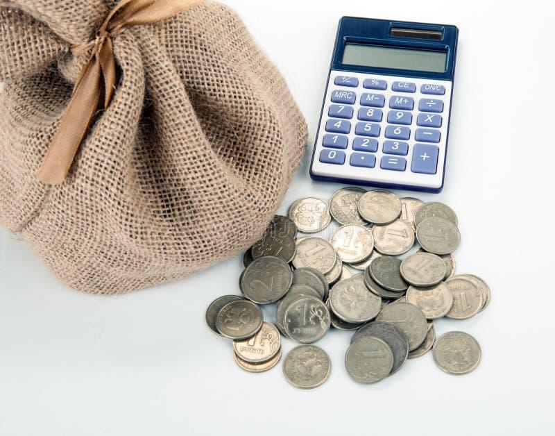 Monedas y calculadora de la rublo rusa con el bolso del dinero en una tabla blanca fotos de archivo