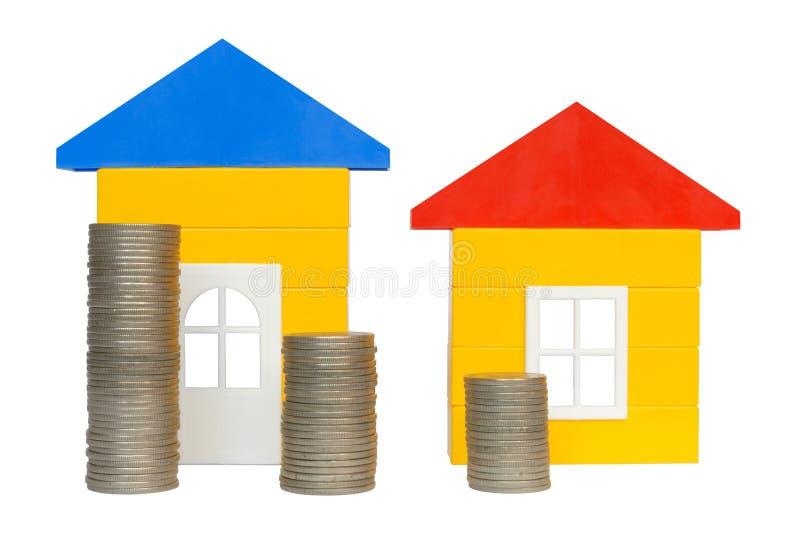 Monedas y casas imagen de archivo