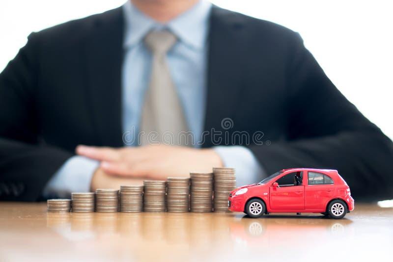 Monedas y coche apilados cada vez mayores de protecci?n de la persona imagenes de archivo