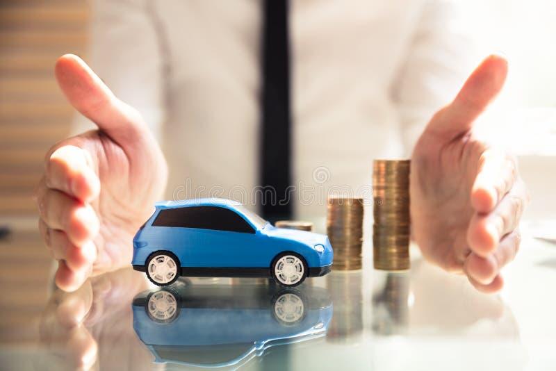 Monedas y coche apilados cada vez mayores de protecci?n de la persona imagen de archivo libre de regalías