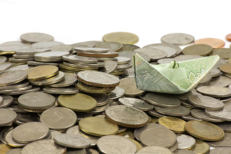 Monedas y cuenta de la moneda de Tailandia dobladas a las naves Arte de la papiroflexia Dinero de Tailandia en el fondo blanco imagen de archivo libre de regalías