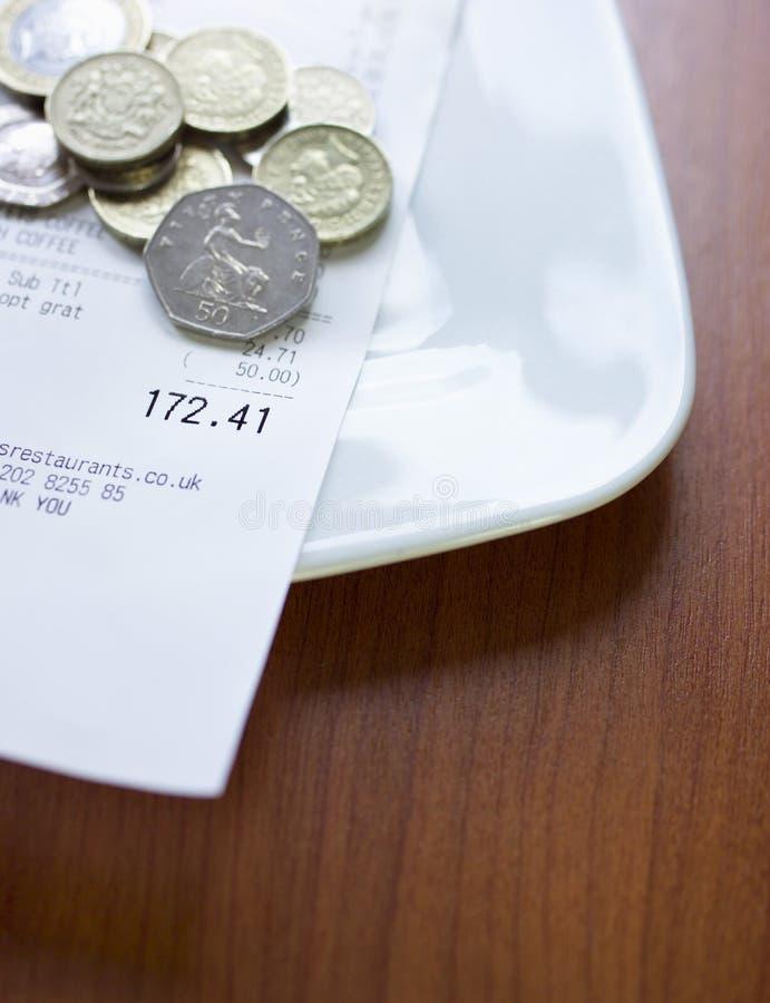 Monedas y cuenta de libra en el primer de la placa fotos de archivo libres de regalías