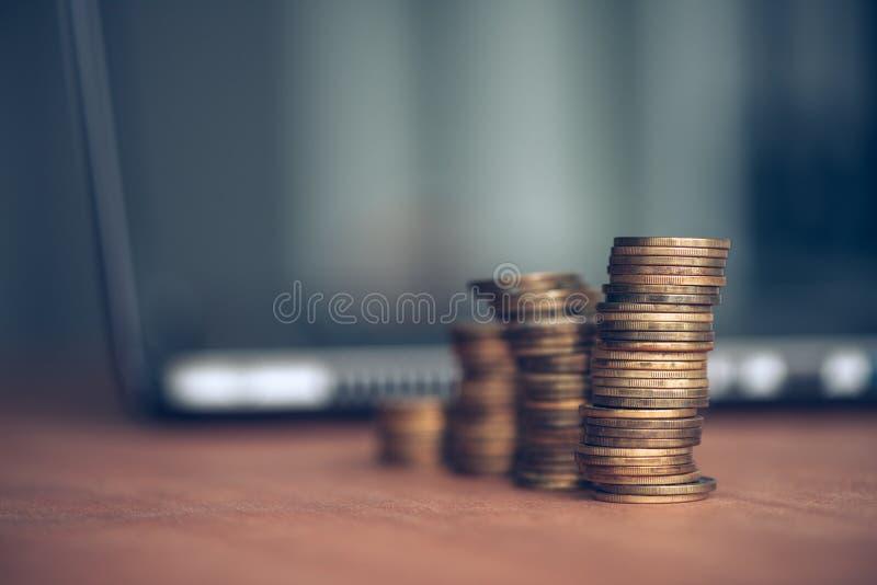 Monedas y ordenador portátil apilados del dinero fotos de archivo libres de regalías