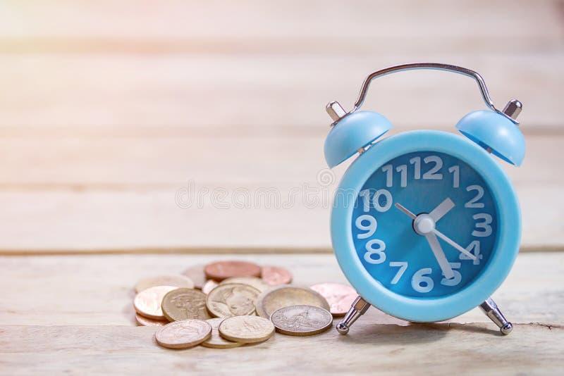 Monedas y reloj azul del alram en el fondo de madera de la tabla fotos de archivo