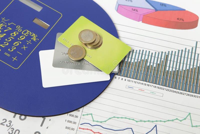 Monedas y tarjetas de crédito en un documento con algunos gráficos imagenes de archivo