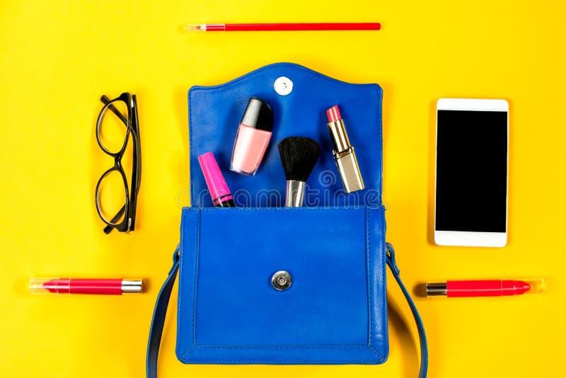 Monedero de la mujer, productos de belleza, smartphone, vidrios en un fondo amarillo brillante, visión superior fotografía de archivo libre de regalías