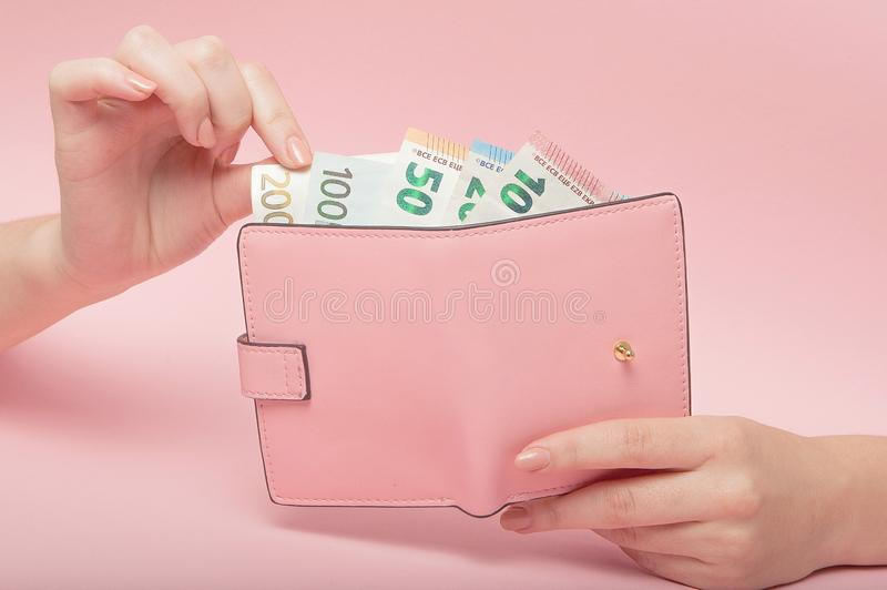 Monedero rosado y billetes de banco euro en manos femeninas en fondo rosado Concepto e Instagram del negocio foto de archivo