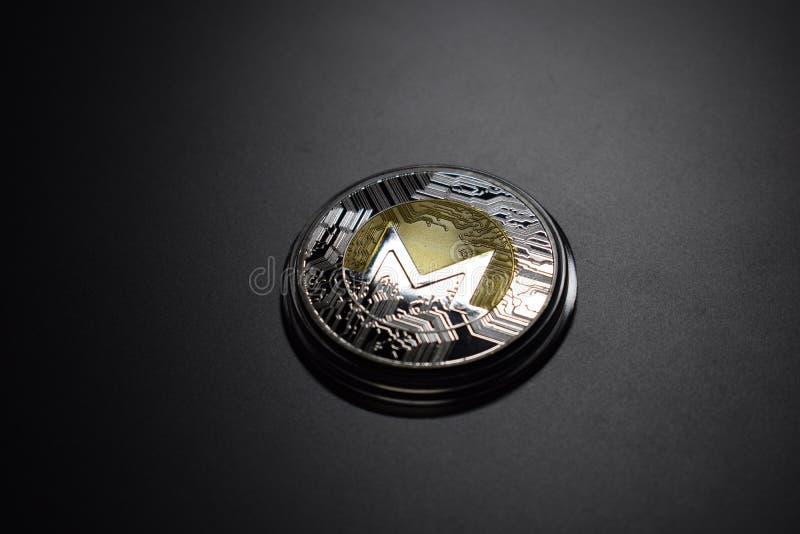 Monero cryptocurrency moneta otaczająca ciemnym tłem zdjęcie stock