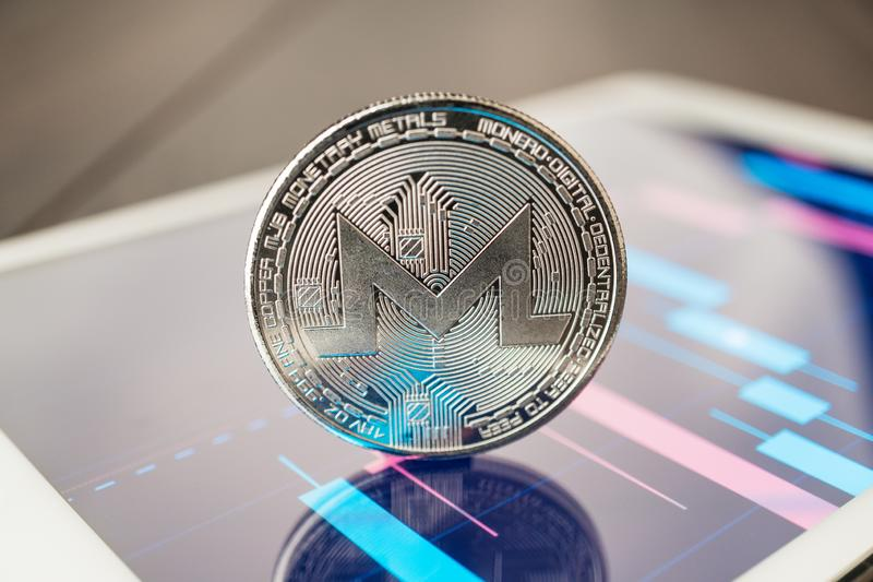 Close-up photo of monero cryptocurrency physical coin on the tablet computer showing stock market charts. trading monero crypto. Coin concept on the wooden table stock images