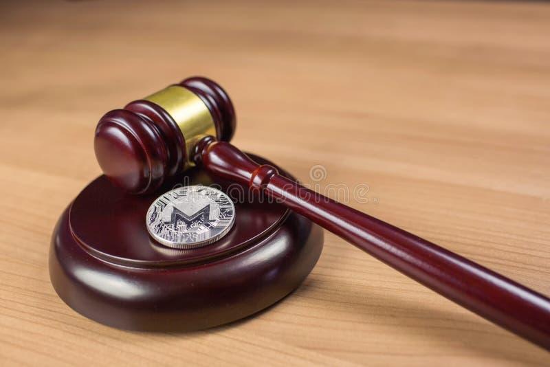 Monero mynt och auktionsklubba p? ett skrivbord arkivfoto