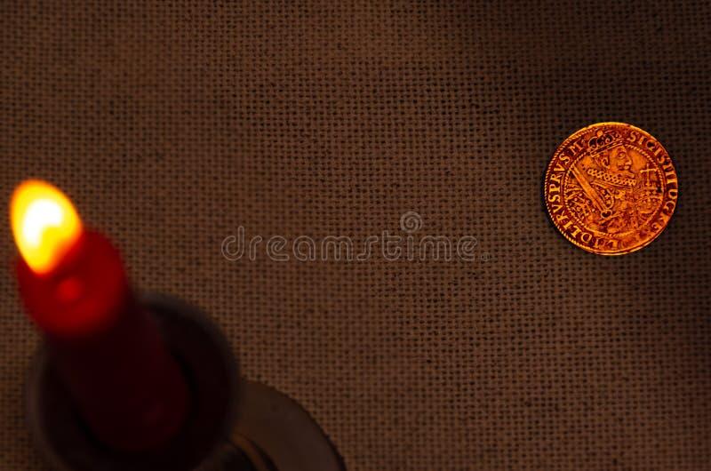 Moneta d'argento antica e candela bruciante fotografia stock