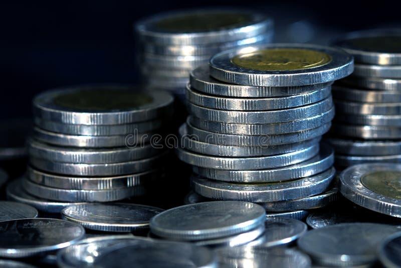 Moneta d'argento dei soldi che impila sul fondo scuro fotografia stock