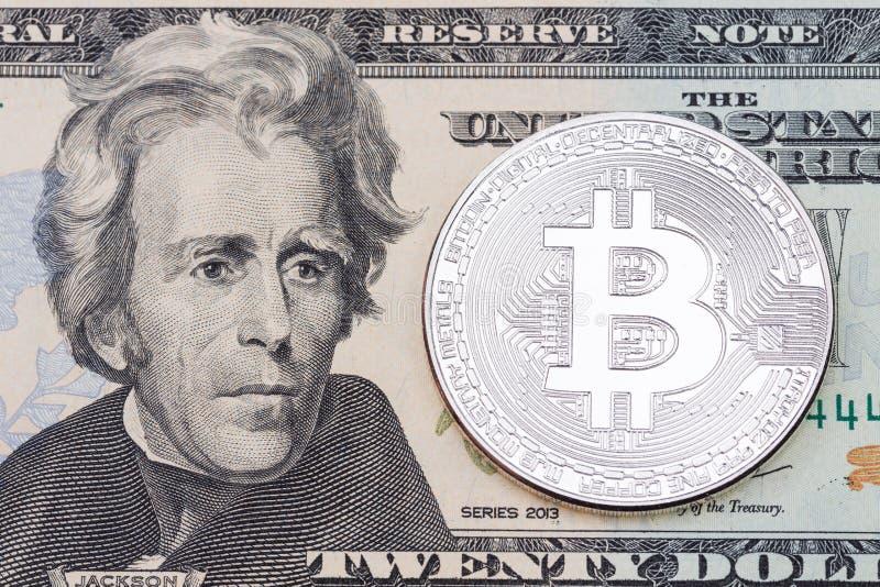 Moneta d'argento del bitcoin su un dollaro di fine della banconota su fotografia stock