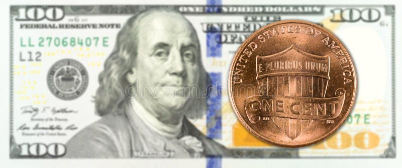 1 moneta del centesimo contro il complemento della banconota da 100 dollari americani fotografie stock libere da diritti