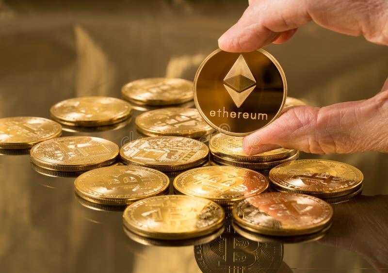 Moneta dell'etere della tenuta della mano sopra i bitcoins fotografia stock libera da diritti