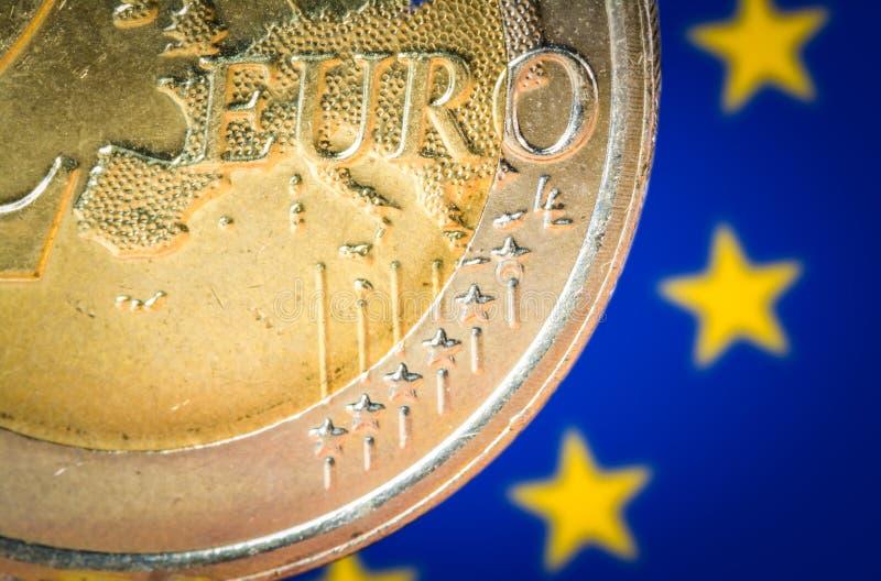 Moneta dell'euro 2 con una bandiera vaga dell'UE sui precedenti immagine stock