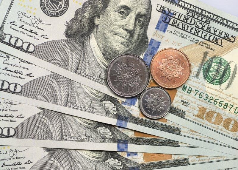 Moneta dell'Oman del rial sopra le banconote in dollari immagini stock libere da diritti