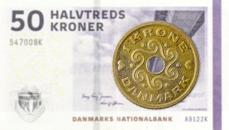 1 moneta della corona danese contro una nota di 50 corone danesi fotografie stock libere da diritti