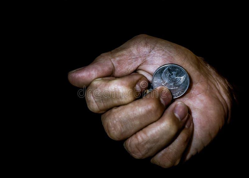 Moneta della rupia dell'Indonesia nella mano di una persona asiatica isolata immagini stock libere da diritti