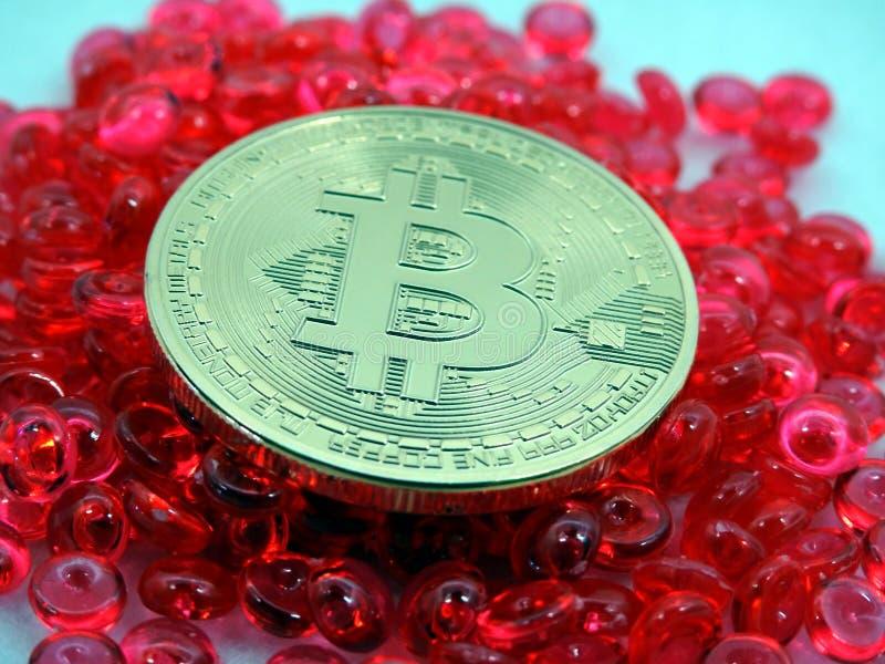 Moneta di Bitcoin sopra i battiti rossi fotografia stock