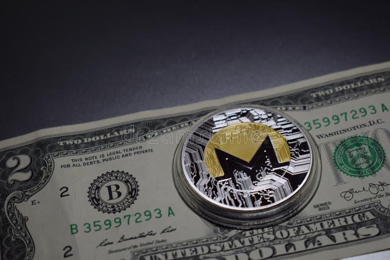 Moneta di cryptocurrency di Monero su due dollari di banconota fotografia stock