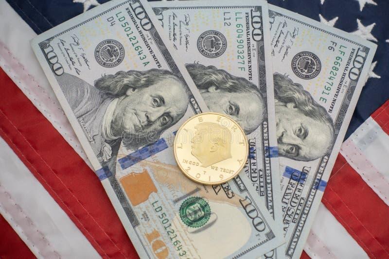 Moneta di Donald Trump contro un fondo di $100 fatture e della bandiera degli Stati Uniti fotografia stock libera da diritti