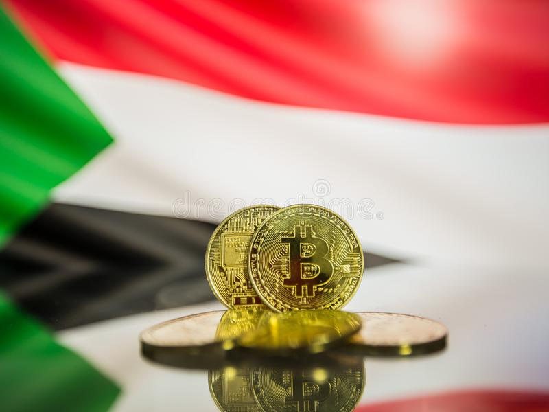 Moneta di oro di Bitcoin e bandiera defocused del fondo del Sudan Concetto virtuale di cryptocurrency immagini stock