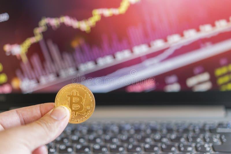 Moneta di oro di Bitcoin e fondo defocused del grafico Concetto virtuale di cryptocurrency Bitcoin è una moneta di oro e grafici  fotografia stock libera da diritti