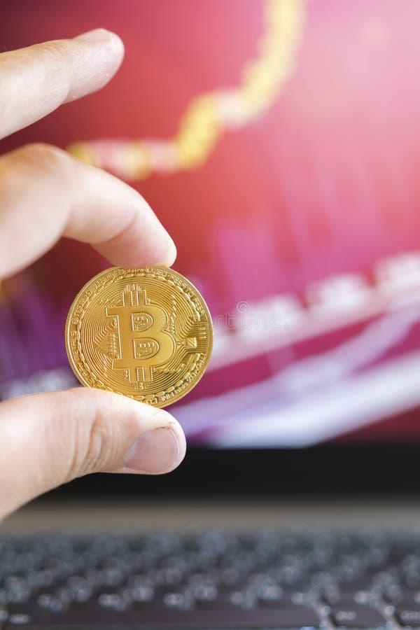 Moneta di oro di Bitcoin e fondo defocused del grafico Concetto virtuale di cryptocurrency Bitcoin è una moneta di oro e grafici  fotografie stock