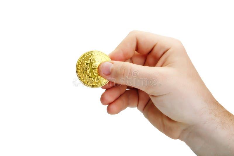 Moneta di oro di Bitcoin in sua mano Un oggetto isolato fotografia stock