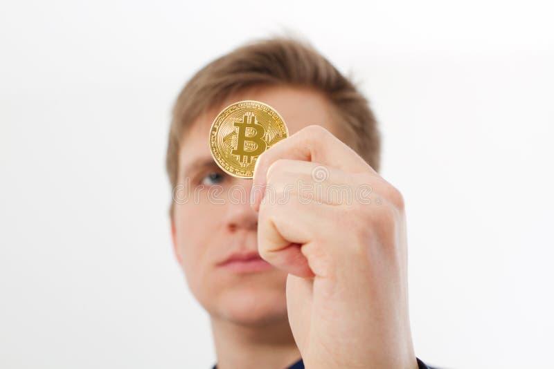 Moneta dorata del bitcoin con il simbolo dell'oro in mano dell'uomo isolata su fondo bianco Uomo d'affari e concetto di successo  fotografia stock libera da diritti