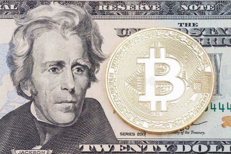 Moneta dorata del bitcoin su venti dollari di fine della banconota su immagine stock