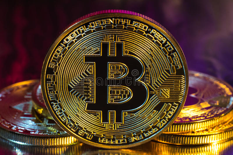 Moneta dorata fisica del bitcoin di Cryptocurrency su fondo variopinto immagine stock
