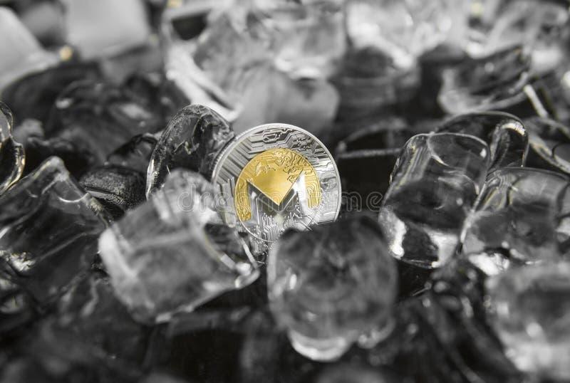 Moneta fisica di monero dell'oro del metallo di valuta di Digital sul fondo del ghiaccio Il concetto dello scambio nell'inverno f fotografia stock