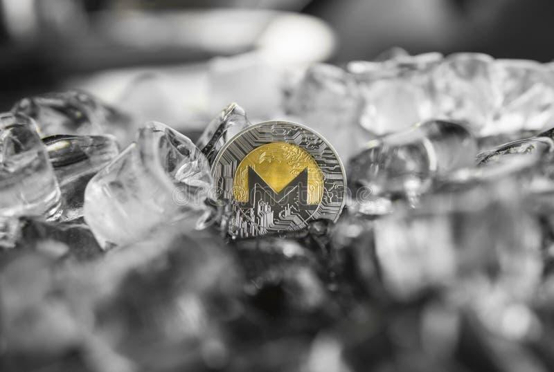 Moneta fisica di monero dell'oro del metallo di valuta di Digital sul fondo del ghiaccio Il concetto dello scambio nell'inverno f immagini stock libere da diritti