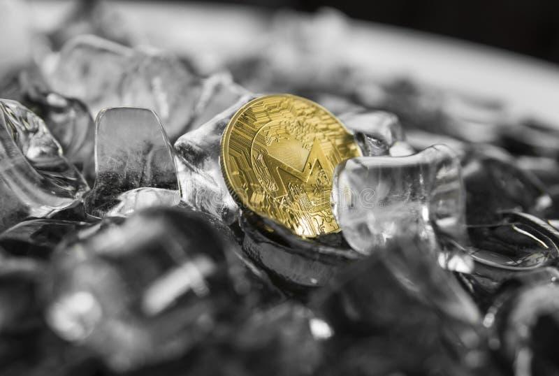 Moneta fisica di monero dell'oro del metallo di valuta di Digital sul fondo del ghiaccio Il concetto dello scambio nell'inverno f fotografie stock libere da diritti