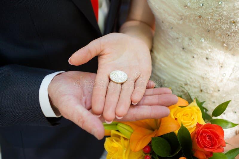 Moneta per fortuna in mani la persona appena sposata immagini stock