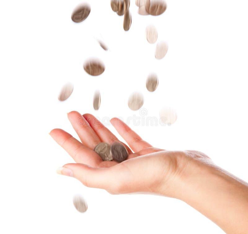 Monete che cadono a disposizione fotografia stock