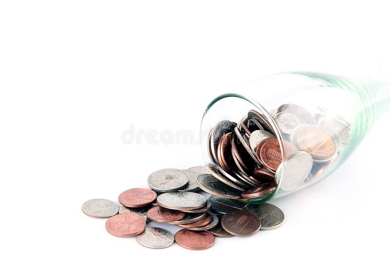 Monete che escono dal vetro immagini stock libere da diritti