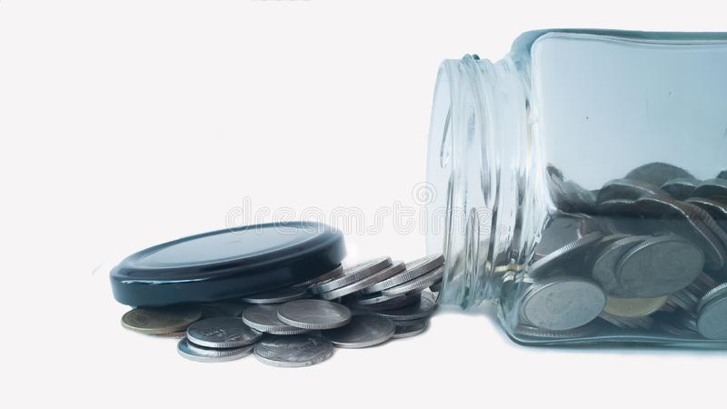 Monete che stanno uscendo dal barattolo fotografia stock