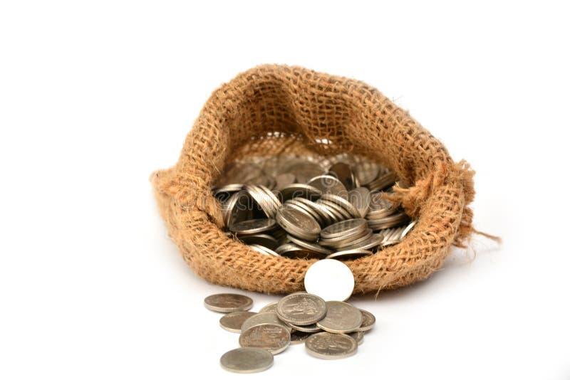 Monete dei soldi in borsa isolata su bianco fotografie stock