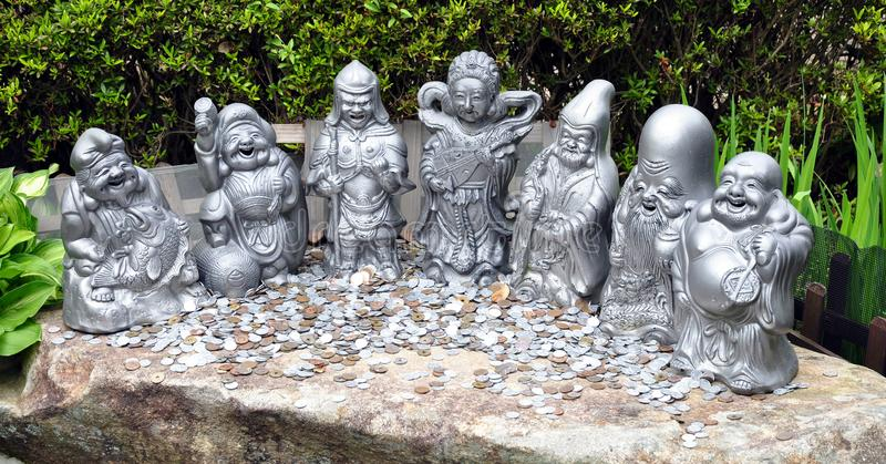 Monete dei soldi e sette statue fortunate dei Daisho-nel tempio, isola Giappone di Miyajima immagine stock