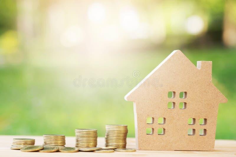 Monete dei soldi impilate su a vicenda nelle posizioni e nella casa differenti in cartamodello riciclato marrone sulla tavola di  immagine stock