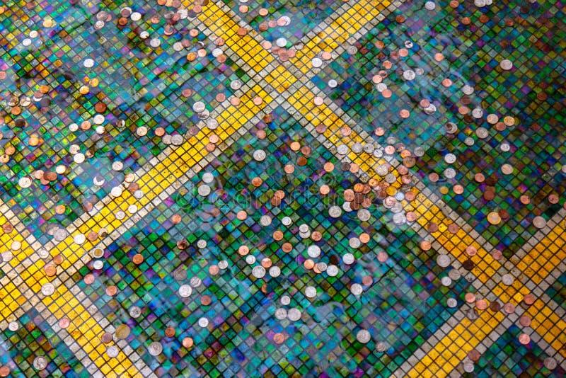 Monete del fondo sparse sulle mattonelle colorate luminose fotografia stock