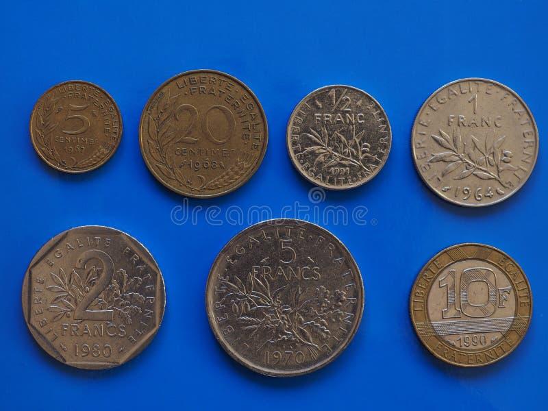 Monete del franco francese, Francia sopra il blu immagini stock