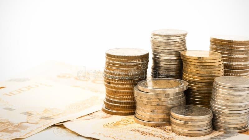 Monete di baht tailandese sul fondo dei soldi della banconota fotografia stock